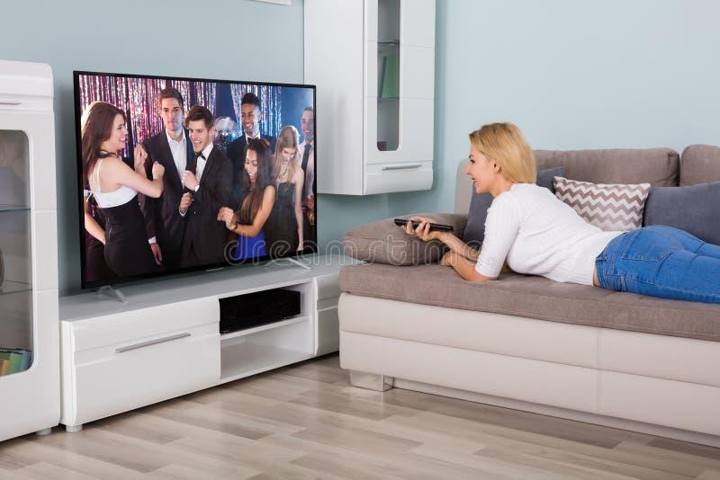 Hållande ögonen på film för kvinna på television royaltyfri bild