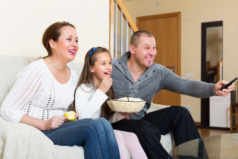 Hållande ögonen på film för lycklig familj royaltyfri foto