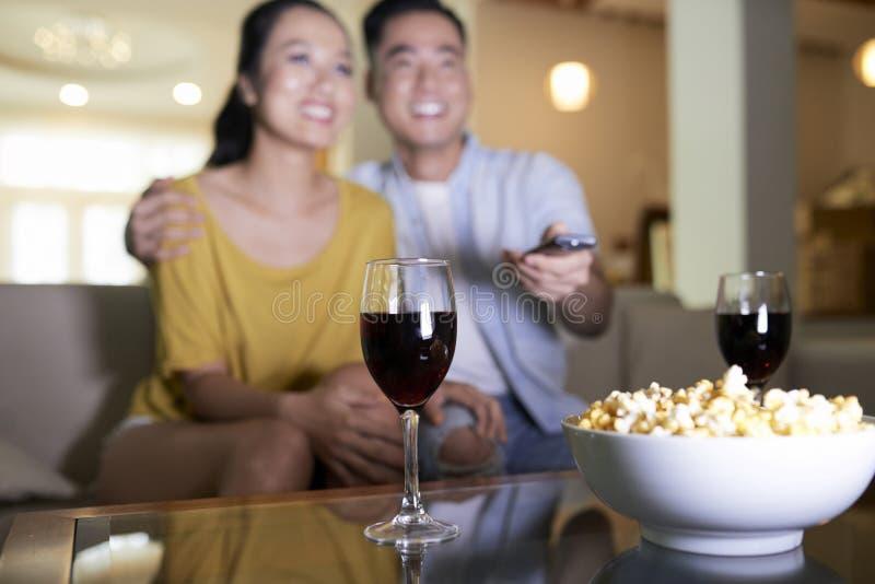 Hållande ögonen på film för lyckliga par hemma arkivfoton