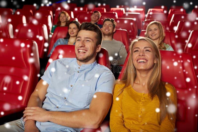 Hållande ögonen på film för lyckliga par i teater arkivbild