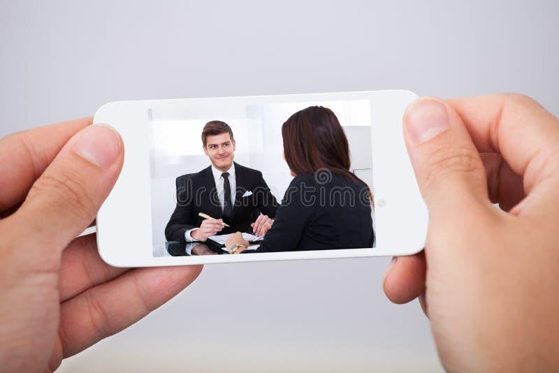 Hållande ögonen på film för man på den smarta telefonen arkivbilder