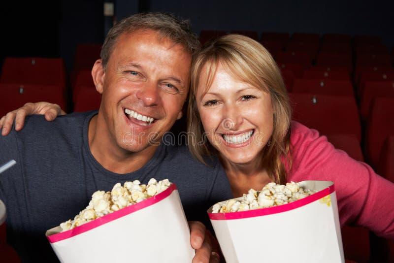 Hållande ögonen på film för par i bio royaltyfria foton