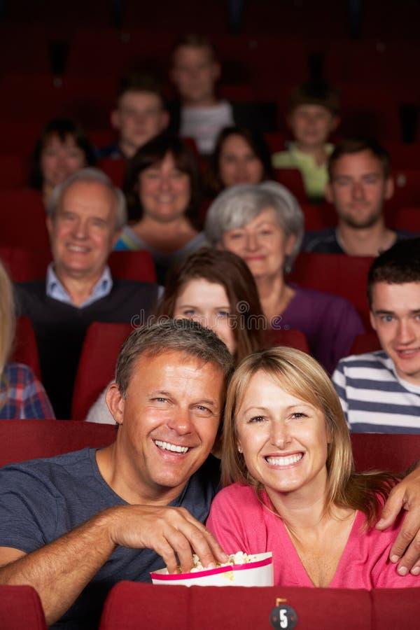 Hållande ögonen på film för par i bio royaltyfri foto
