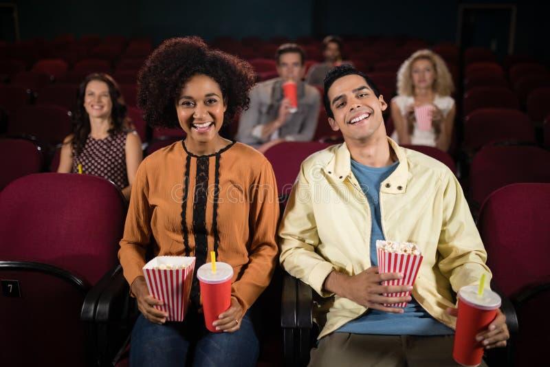 Hållande ögonen på film för par i teater royaltyfria foton