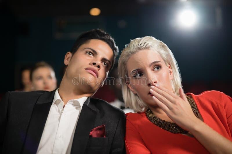 Hållande ögonen på film för par i teater fotografering för bildbyråer