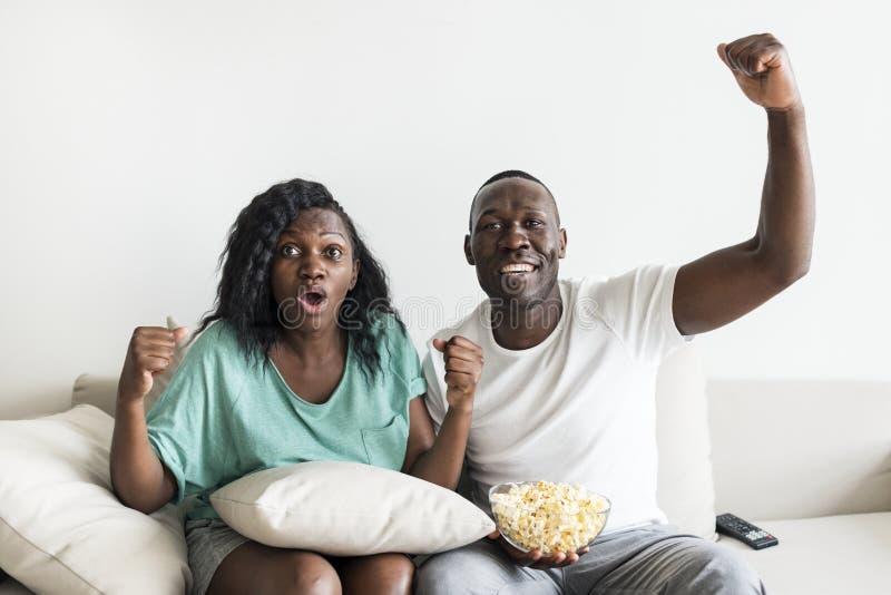 Hållande ögonen på film för svarta par tillsammans hemma royaltyfri bild