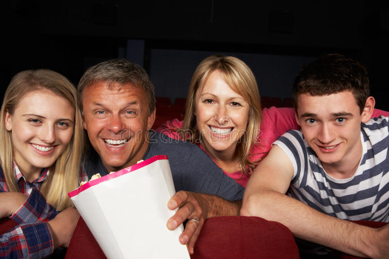 Hållande ögonen på film för tonårs- familj i bio royaltyfri bild