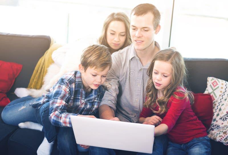 Hållande ögonen på film för ung positiv familj på bärbara datorn tillsammans hemma royaltyfri bild