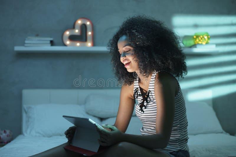 Hållande ögonen på film för ung svart kvinna med bärbara datorn på natten arkivfoto
