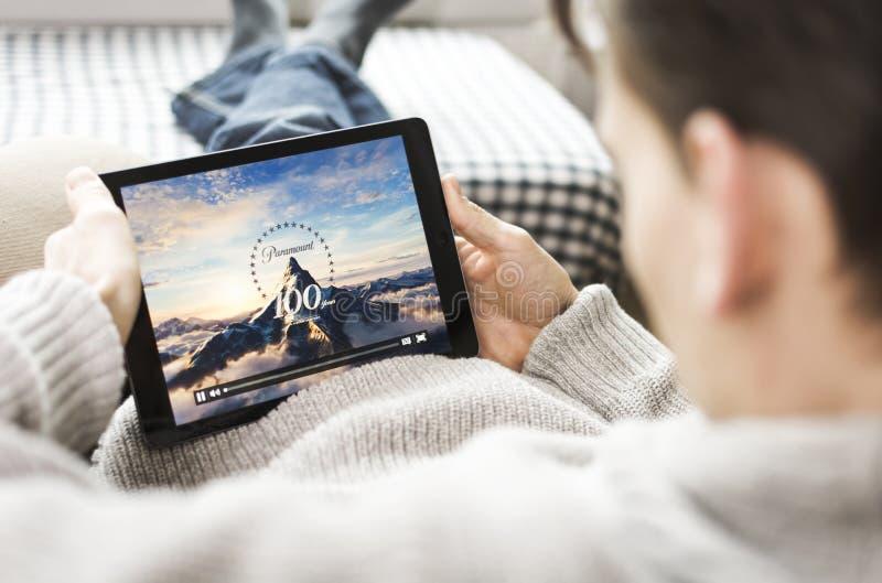 Hållande ögonen på film på iPad. Paramount Pictures royaltyfri fotografi
