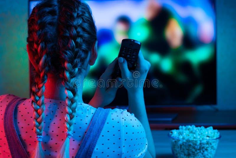 Hållande ögonen på filmer för en ung flicka med en fjärrkontroll med en bunke av popcorn på bakgrunden av TV:N En ljus färg av lj royaltyfria foton