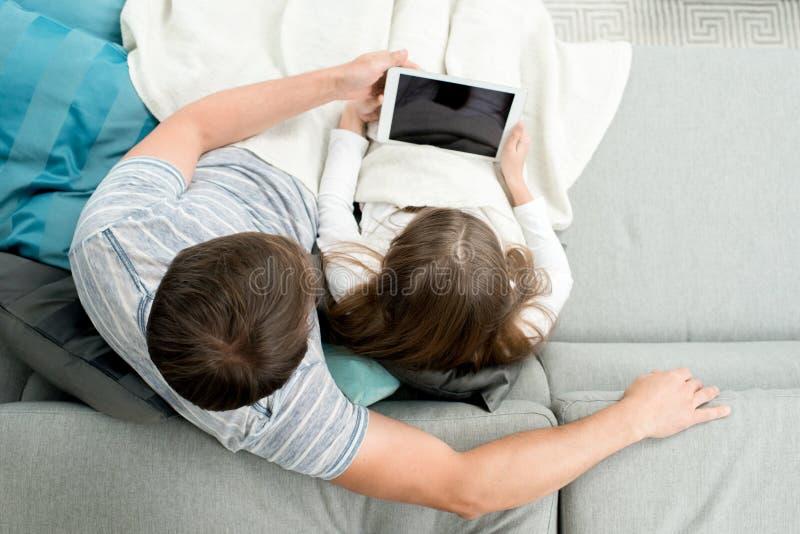 Hållande ögonen på filmer för fader och för dotter arkivfoton