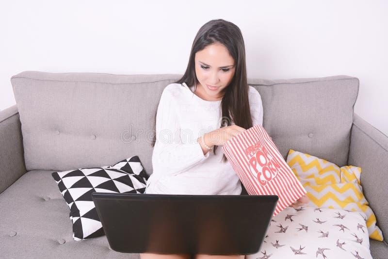 Hållande ögonen på filmer för kvinna med bärbara datorn royaltyfri foto
