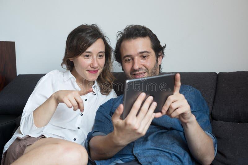 Hållande ögonen på filmer för lyckliga par på den digitala minnestavlan fotografering för bildbyråer