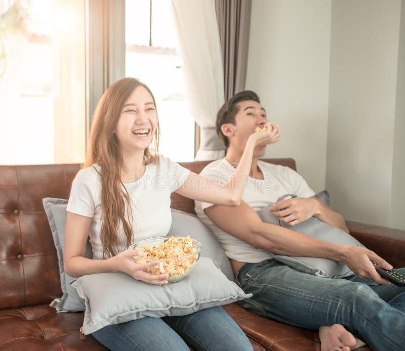 Hållande ögonen på filmsammanträde för asiatiska par på en soffa hemma som är gladlynt, och tagandepopcorn till pojkevännen arkivfoto