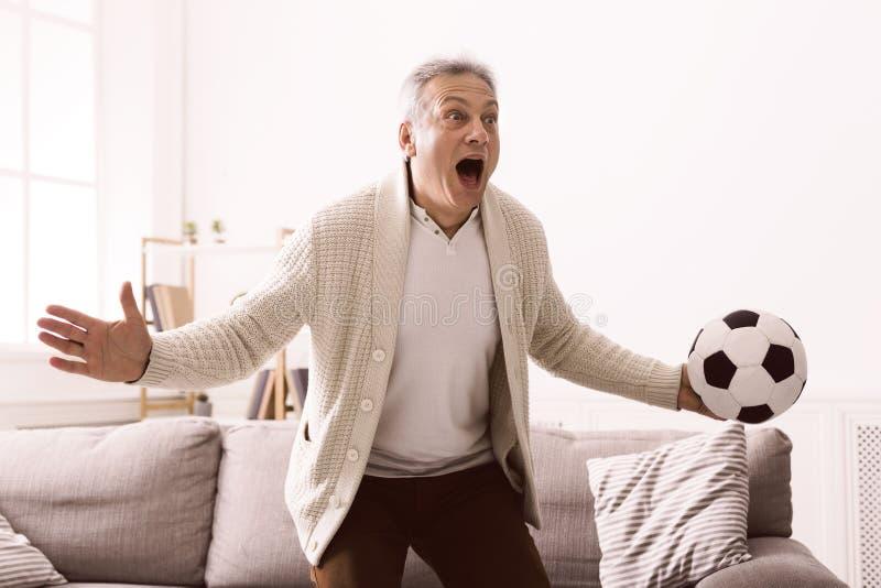 Hållande ögonen på fotboll för emotionell mogen man på television royaltyfri bild