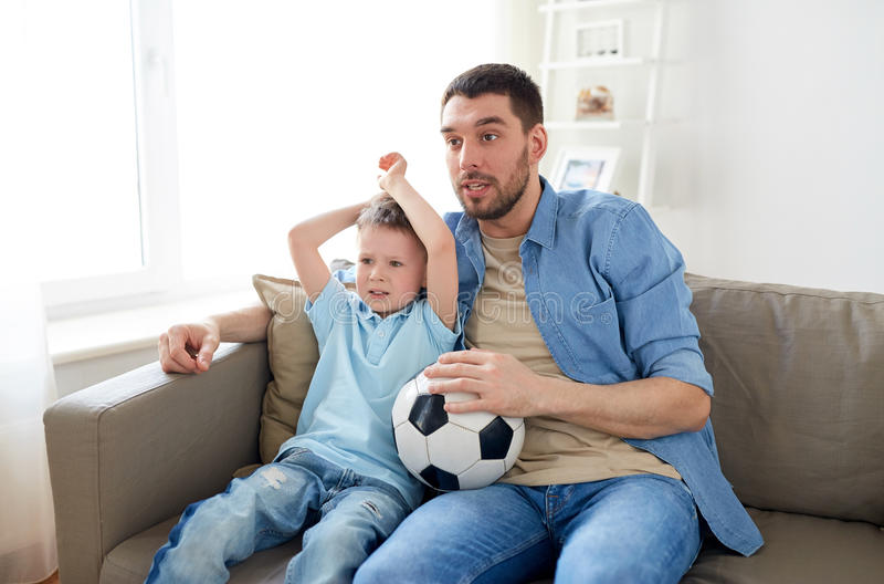 Hållande ögonen på fotboll för fader och för son på tv hemma arkivbild