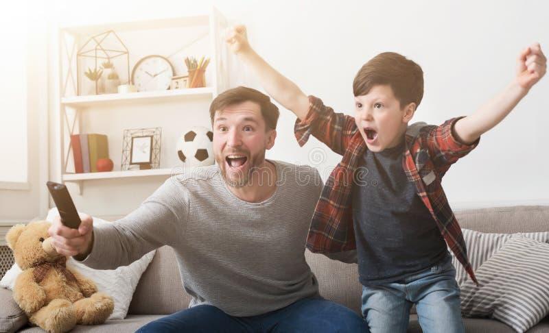 Hållande ögonen på fotboll för fader och för son på TV hemma royaltyfri bild