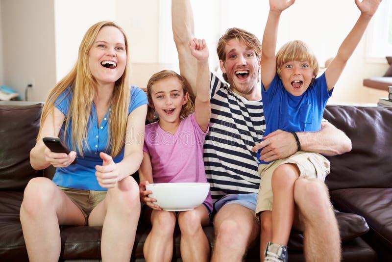 Hållande ögonen på fotboll för familj på TV som firar mål royaltyfri bild