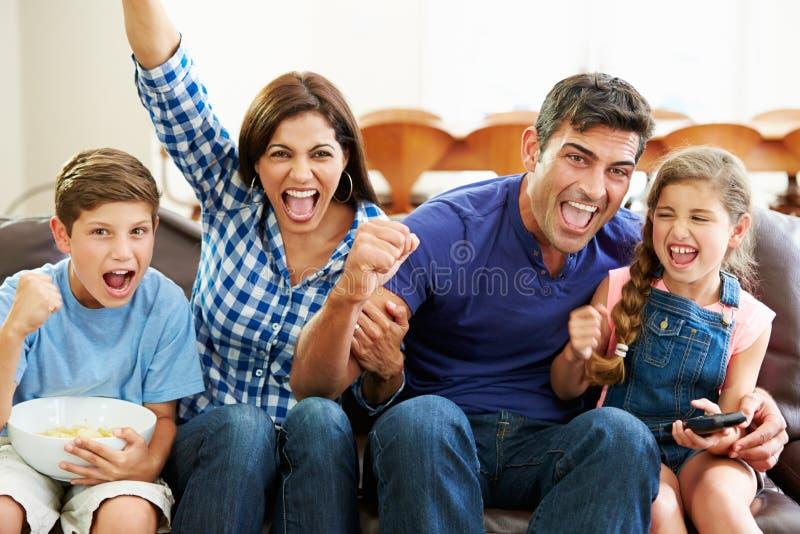 Hållande ögonen på fotboll för familj som firar mål royaltyfria foton