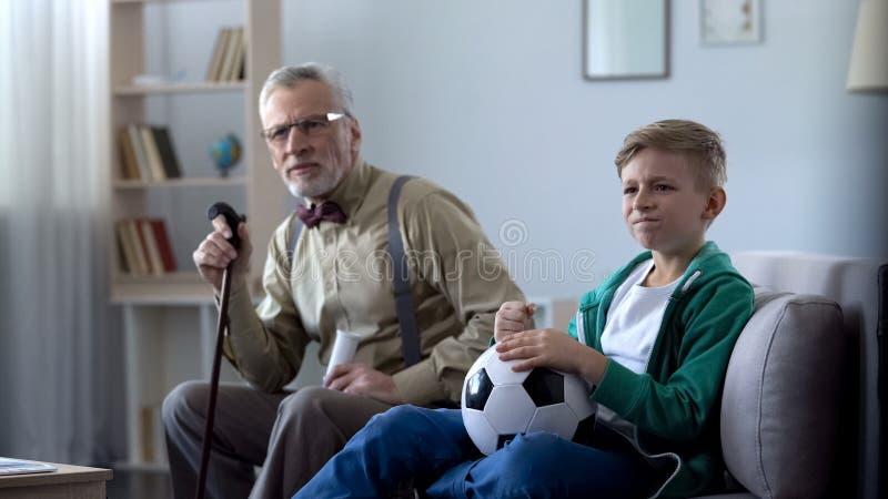 Hållande ögonen på fotboll för farfar och för sonson tillsammans hemma, rubbning över förlust arkivfoto