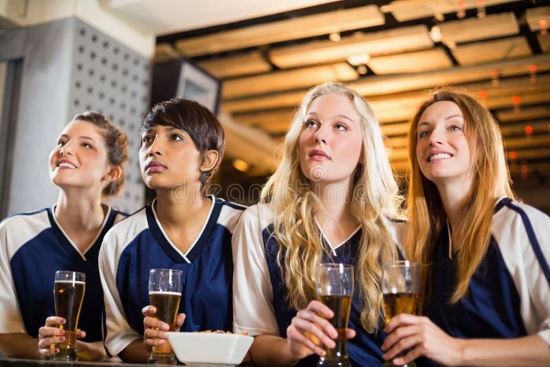 Hållande ögonen på fotboll för kvinnlig fan på stångräknaren fotografering för bildbyråer
