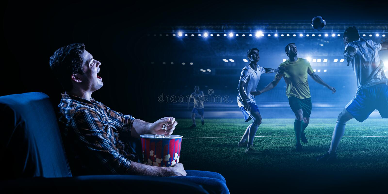 Hållande ögonen på fotboll för ung man på den stora skärmen royaltyfri foto
