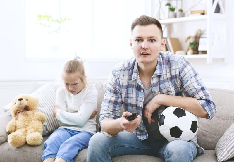 Hållande ögonen på fotboll för upphetsad fader och för ledsen dotter royaltyfria foton