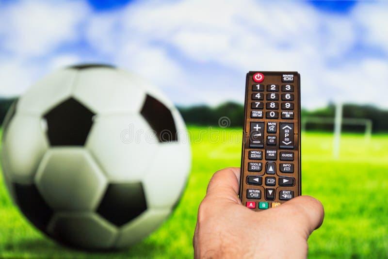 Hållande ögonen på fotboll-/fotbolllek på modern tv, med en närbild av royaltyfria bilder