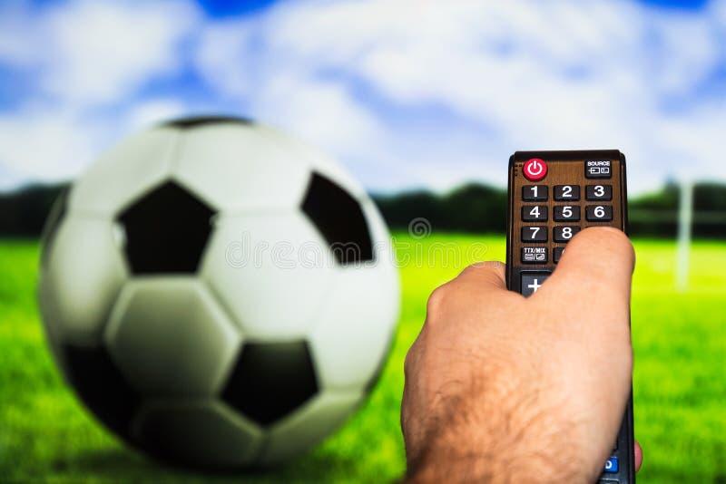 Hållande ögonen på fotboll-/fotbolllek på modern tv, med en närbild av royaltyfri bild