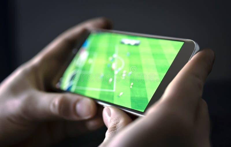 Hållande ögonen på fotboll- och sportström med mobiltelefonen Man som direktanslutet strömmar levande videopp omspel för fotbolll royaltyfria foton