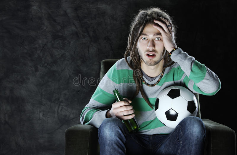 Hållande ögonen på fotboll på tv:n arkivfoto