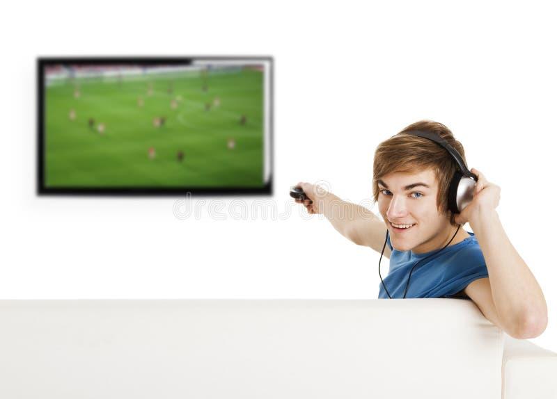 Hållande ögonen på fotboll på TV:N royaltyfri bild