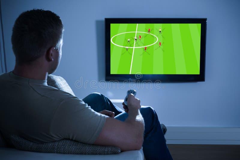 Hållande ögonen på fotbolllek för man på television hemma royaltyfri foto