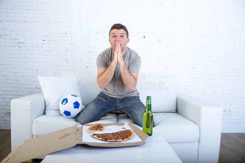 Hållande ögonen på fotbolllek för ung man på guden för nervös och upphetsad lidandespänning för television den be för mål royaltyfri bild