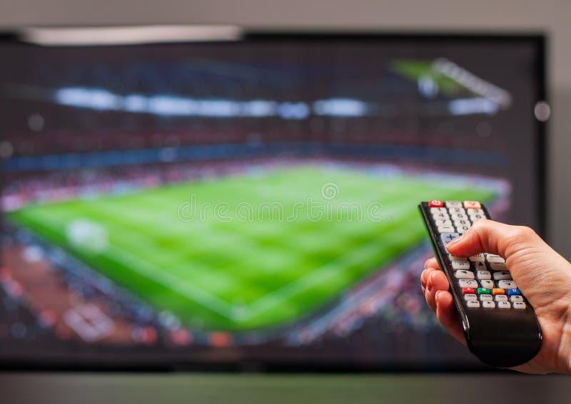 Hållande ögonen på fotbollsmatch för man på television, fjärrkontrollen i hand arkivbild