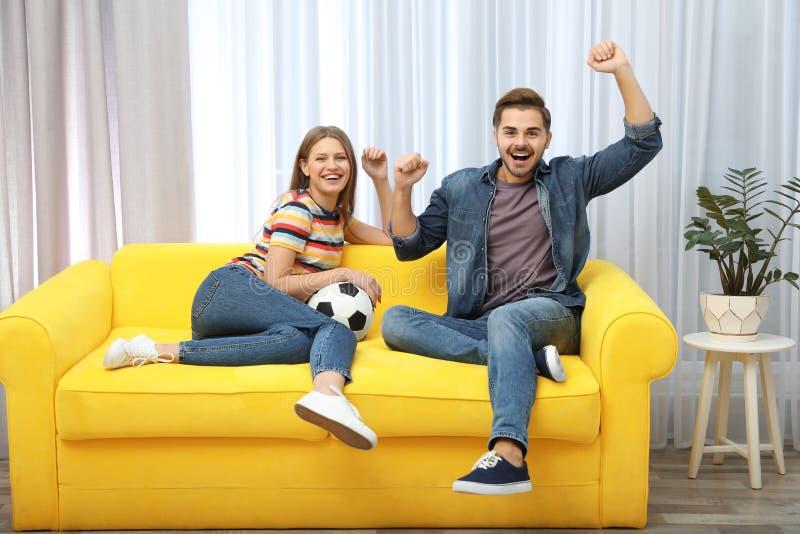 Hållande ögonen på fotbollsmatch för par på TV fotografering för bildbyråer