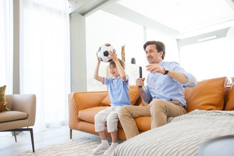 Hållande ögonen på fotbollsmatch för pojke med fadern royaltyfri foto
