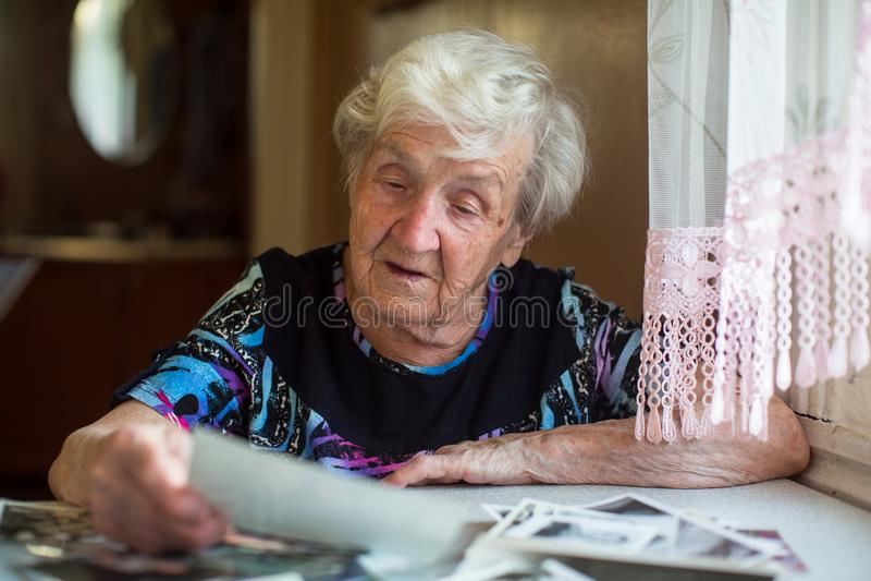 Hållande ögonen på foto för äldre ensam kvinna som sitter på tabellen royaltyfri bild