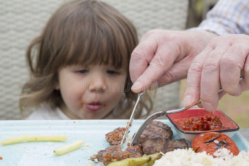 Hållande ögonen på händer för barn som klipper köttbullar arkivfoto