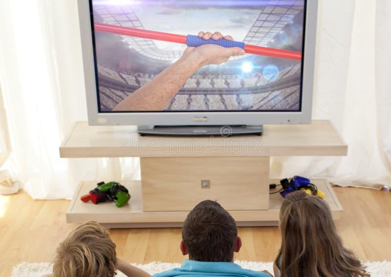 Hållande ögonen på kastspjutkast för familj på television hemma fotografering för bildbyråer
