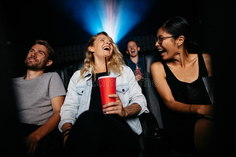 Hållande ögonen på komedifilm för grupp människor i teater arkivfoto