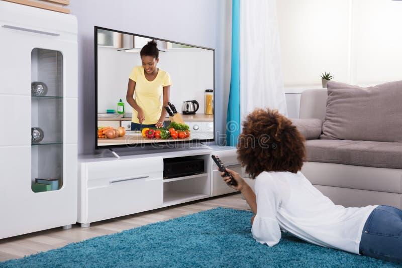 hållande ögonen på kvinna för television arkivbild