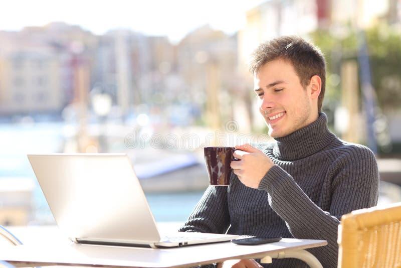 Hållande ögonen på massmedia för Smileyman i en bärbar dator i en stång royaltyfria foton