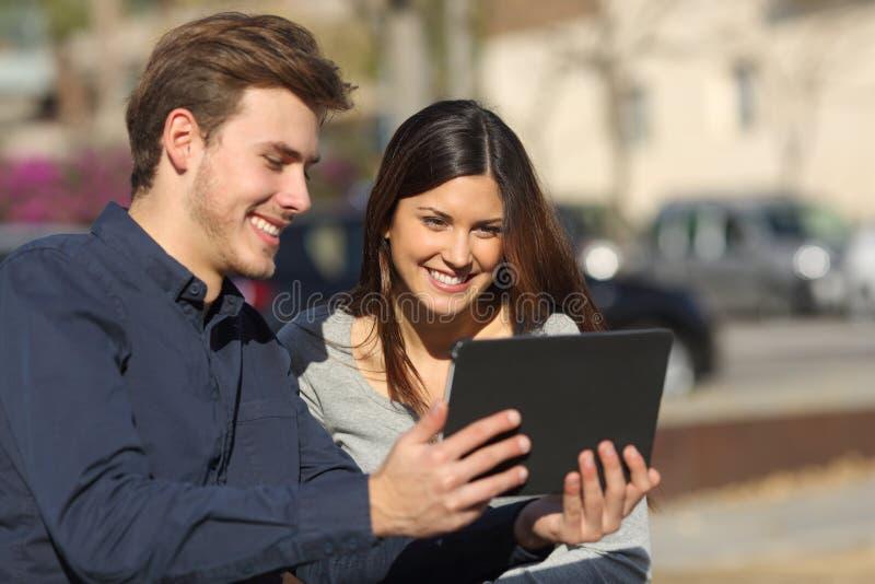 Hållande ögonen på massmediainnehåll för par i en minnestavla utomhus fotografering för bildbyråer