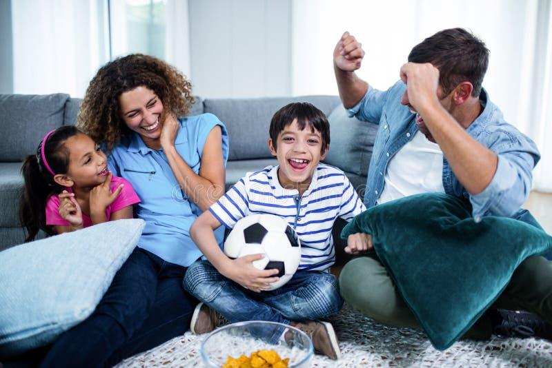 Hållande ögonen på match för familj tillsammans på television royaltyfri fotografi