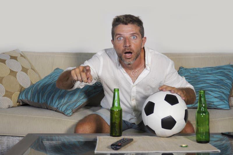 Hållande ögonen på match för passionerad fotbollsfansupporterman på televisi royaltyfri bild