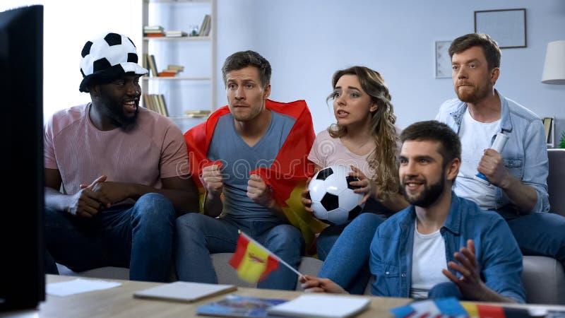 Hållande ögonen på match för spanska vänner på tv hemma och att stötta laget, samhörighetskänsla royaltyfri bild