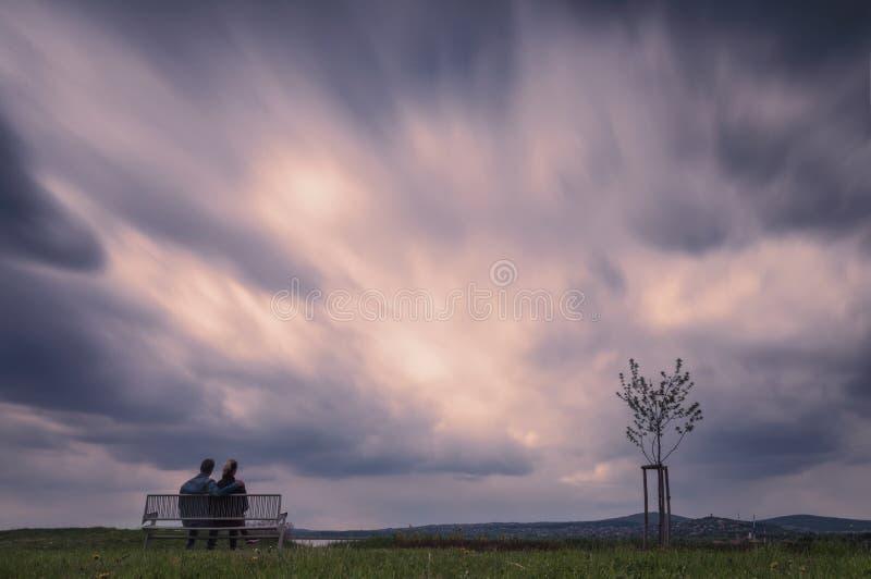 Hållande ögonen på moln för par arkivfoto