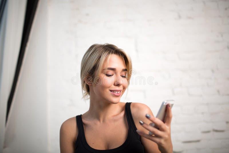 Hållande ögonen på nyheterna för kvinnlig chef på websiten via celltelefonen Hipsterflicka som använder mobiltelefonen arkivbilder